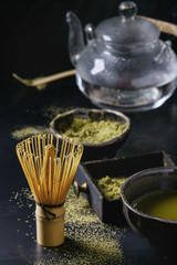 Green tea matcha powder and hot drink in black bowls and wood box standing with glass teapot, bamboo traditional tools spoon, whisk in terracotta tray over dark metal background. Close up