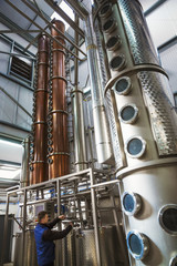 Tall copper distillery chambers in a brewery, brewing storage tanks in copper and steel. A man in overalls checking the gauges.