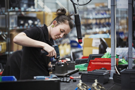 A young woman using a power tool, a skilled factory worker assembling cycle parts.