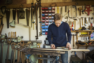 Man working in garden workshop, surrounded by tools