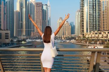 Happy beautiful unrecognizable tourist woman in fashionable summer white dress enjoying in Dubai marina in United Arab Emirates. Luxury and comfortable tourism season in UAE.