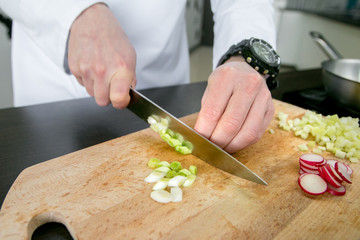 The cook cuts vegetables (green onions) for ratatouille with chicken on a board