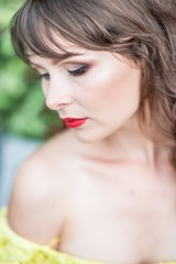 Portrait of a beautiful young woman in a yellow dress with red lipstick. Spring portrait of a girl.