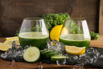 Cucumber raw vegetable juice, green juice in a delicious setting surrounded by cut fruit and vegetables, cold ice, and inspiration for healthy living. Chock full of antioxidants.