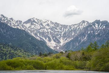 Hotaka mountain range and taisho ike pond in spring at kamikochi national park nagano japan