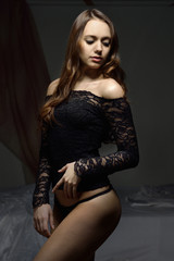 beautifil woman with long brown hair in lace lingerie.