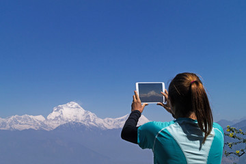 Girl takes pictures of mountains on a tablet.