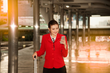 Asian pretty business woman standing with luggage and use smart phone at crossing bridge landmark in Bangkok city.