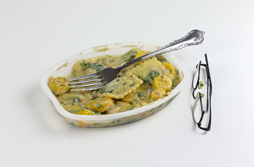 Ravioli with spinach TV dinner with eyeglasses to the side on a white tablecloth.