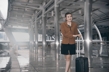 Asian pretty business woman standing with luggage at crossing bridge landmark in Bangkok city.