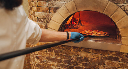 Restaurant chef takes pizza from oven in traditional restaurant.
