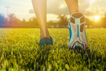 Runner feet practice running on grass closeup on shoe. Fitness and workout wellness concept.
