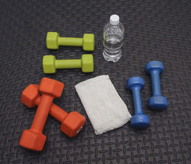 Colorful Hand Weights, Towel And Water On Workout Mat