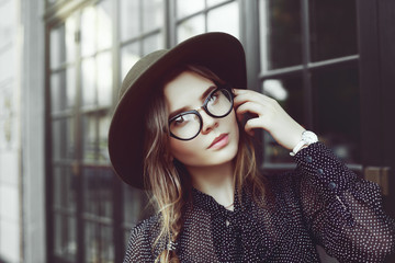 Outdoor close up portrait of young beautiful fashionable girl posing in street. Model wearing trendy cat eye glasses, fedora hat, white wrist watch. Female fashion concept. Copy, empty space for text