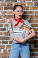 portrait of pensive asian student holding books and pencil
