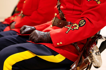 Royal Canadian Mounted Police (RCMP) officers watch cadet badge presentations at a graduation ceremony in Regina