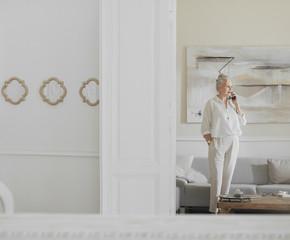 Senior woman standing in Livingroom and talking on mobile phone