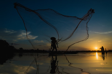 Silhouette Fisherman Fishing Nets on the boat.Thailand