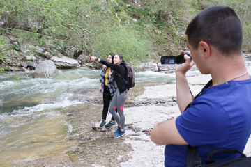 Young travelers standing together by the creek and looking away at a view. A young man is shooting on video