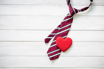 Happy Father's Day inscription with colorful tie and red heart on wooden background floor backround.