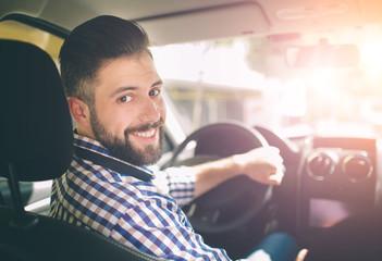 Handsome elegant serious man drives a car Fototapete
