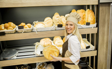 Pretty young woman selling bread in the bakery