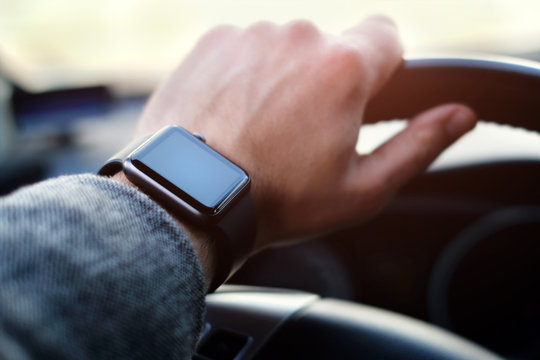 Businessman driving a car with smart watch on the hand