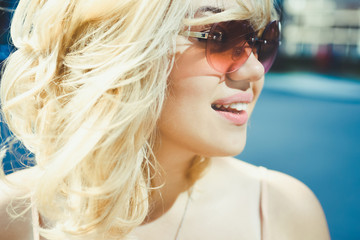 close-up portrait of a beautiful charming girl hipster blonde in sunglasses laughing and posing with full lips