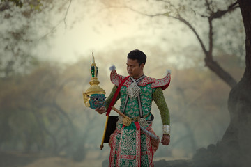 Thailand: The Men in traditional dress character Ramayana story standing in temple holding the mask