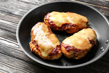 Tasty chicken parmesan with cheese on frying pan, closeup