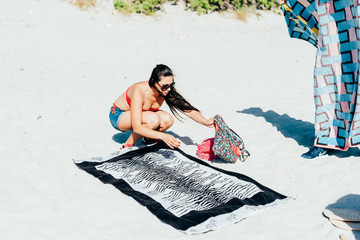 Young woman millennial on the beach with towel - sunbathing, summer activities, leisure concept