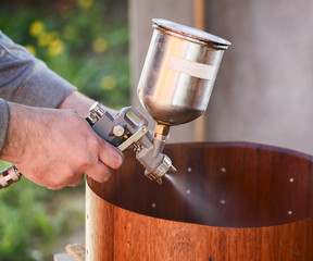 Carpenter spraying lacquer on wooden drum shell