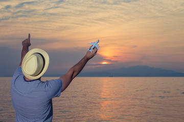 Tuinposter Art Studio Tourist guy holding airplane toy on the beach at sunset. Travel and summer vacation concepts