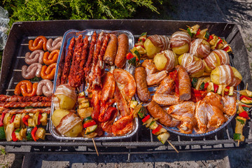 Assorted meat from chicken and pork and various vegetables on barbecue grill cooked for summer family dinner