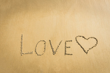 Word Love written on the sand heart drawn message romantic symbol concept