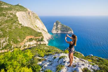 Woman taking photo of cliff - Zakynthos island, Agalas, Greece
