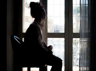 Thoughtful sad woman looking out of window