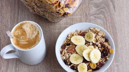 Kaffe mit Müsli und Banane zum Frühstück