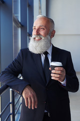 Happy gentleman holding coffee and looking out window