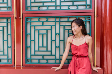 Beautiful asian young woman tourist relaxing on summer holiday sitting near ancient traditional chinese wooden window in china travel destination. Girl in delicate elegant silk sun dress.