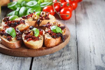 Appetizer bruschetta with sun-dried tomatoes, olives and mozarella.