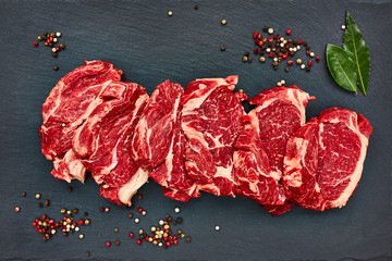 Fresh raw beef steaks with pepper on black slate board/ Copy space, top view.