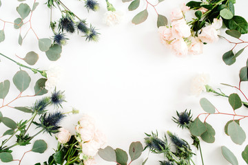 Round frame wreath made of beige rose flowers, eringium flower, eucalyptus branches on white background. Flat lay, top view. Floral background