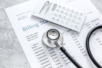 medical treatmant billing statement with stethoscope and calculator on stone background