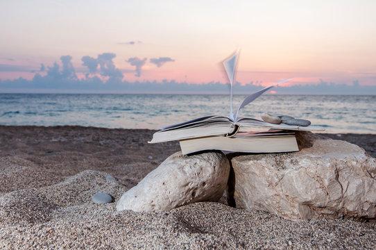 Open book at the beach near the sea during a summer holiday on a sunset
