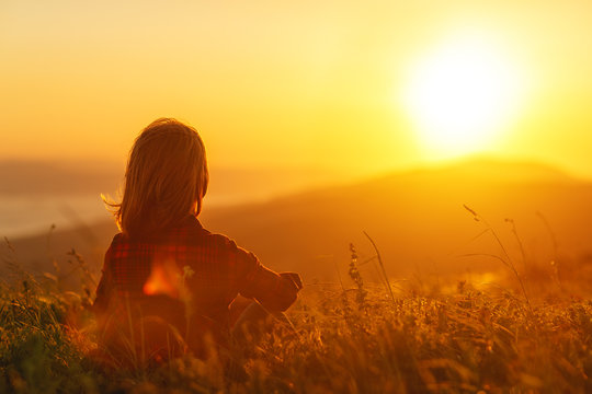 Woman sits with her back in the field and admires the sunset in the mountains.