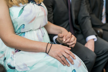 Young married couple holding hands during ceremony wedding day