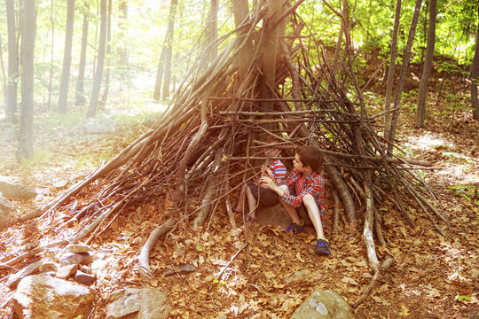 Children play in a hut out of twigs. wooden stick hut house  in the forest