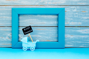 Baby Shower - toy pram with backboard sign with blue frame and wooden background