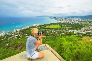 Travel photographer takes a shot of Honolulu and Waikiki beach, Oahu in Hawaii from Diamond Head State Monument. Nature photographer taking pictures outdoors during hawaiian hiking Diamond Head hike.